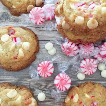 White chocolate and peppermint cookies on a wooden table with peppermint candies and white chocolate pieces