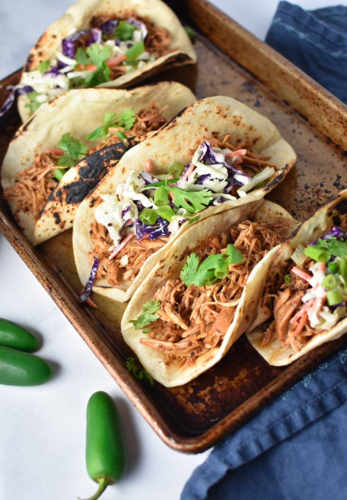 Corn tortillas filled with shredded chicken meat and topped with cilantro and slaw