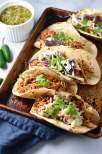 Four shredded chicken tinga tacos on a baking sheet