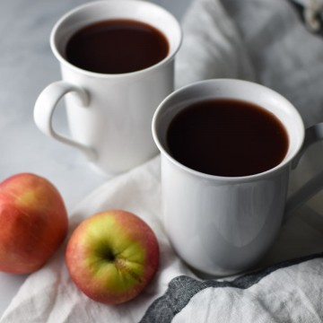 Two cranberry wassail cups with apples on a white table