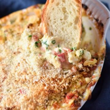 A slice of bread dipping into creamy crab dip