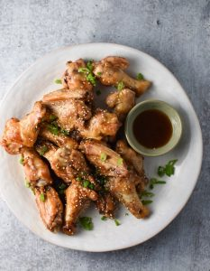 Sesame chicken wings with a dipping sauce and scallions on a grey table