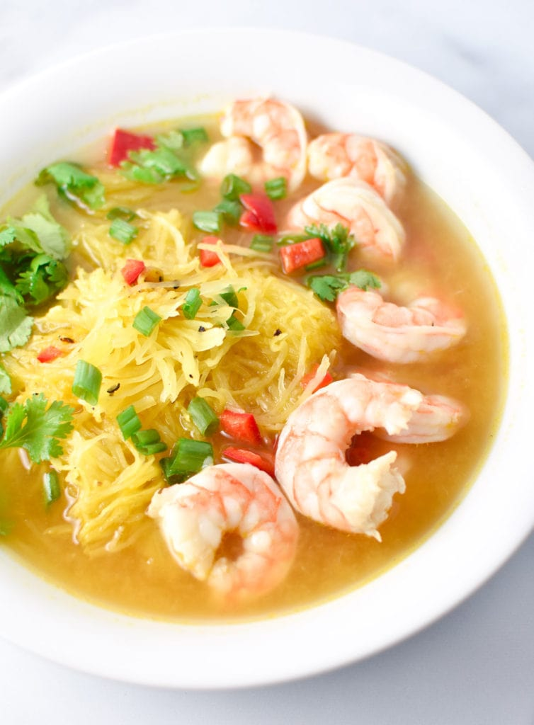 Spaghetti squash soup with shrimp in a white bowl on a marble table
