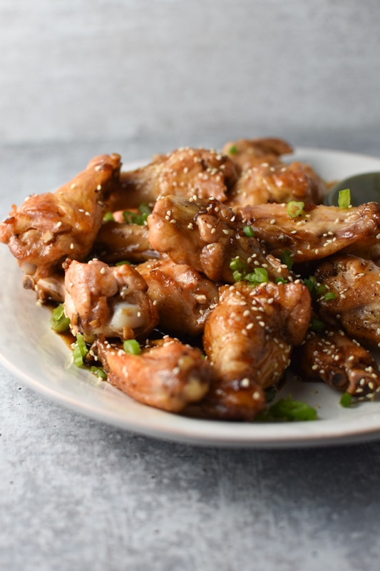 A plate of sesame ginger chicken wings on a grey table