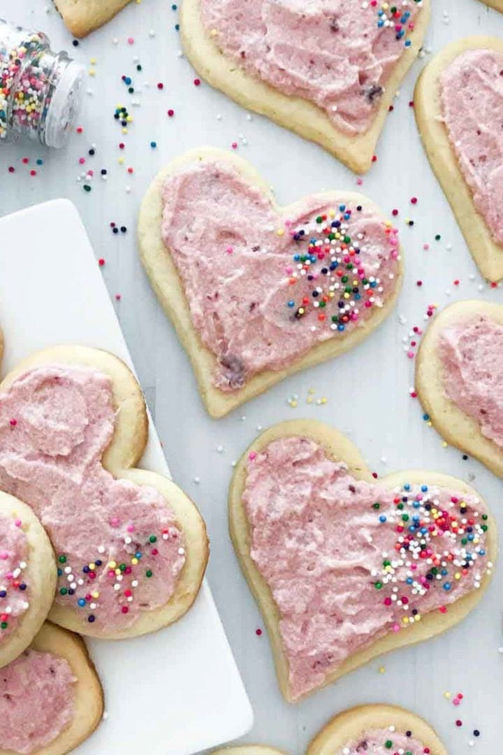Heart shaped sugar cookies with pink cherry frosting and sprinkles on a plate with sprinkles scattered on top