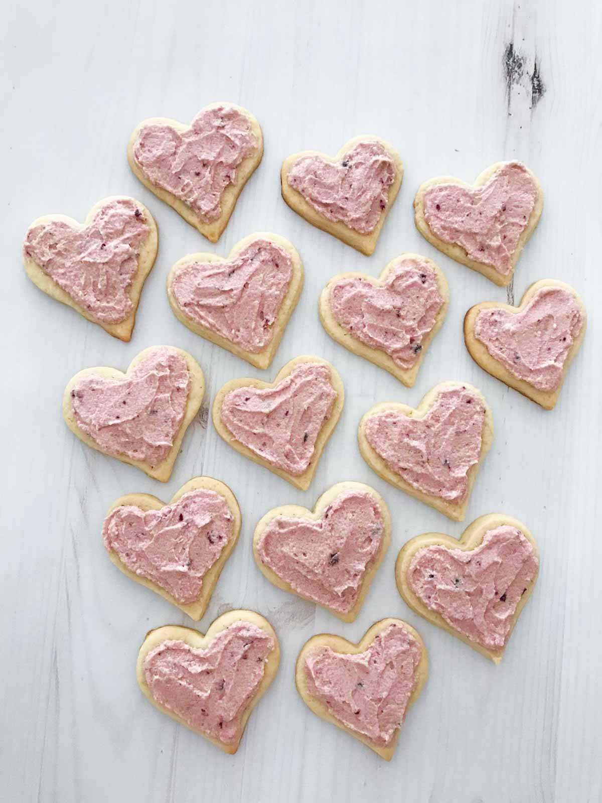 Cream cheese sugar cookies with a pink cherry frosting on a white table