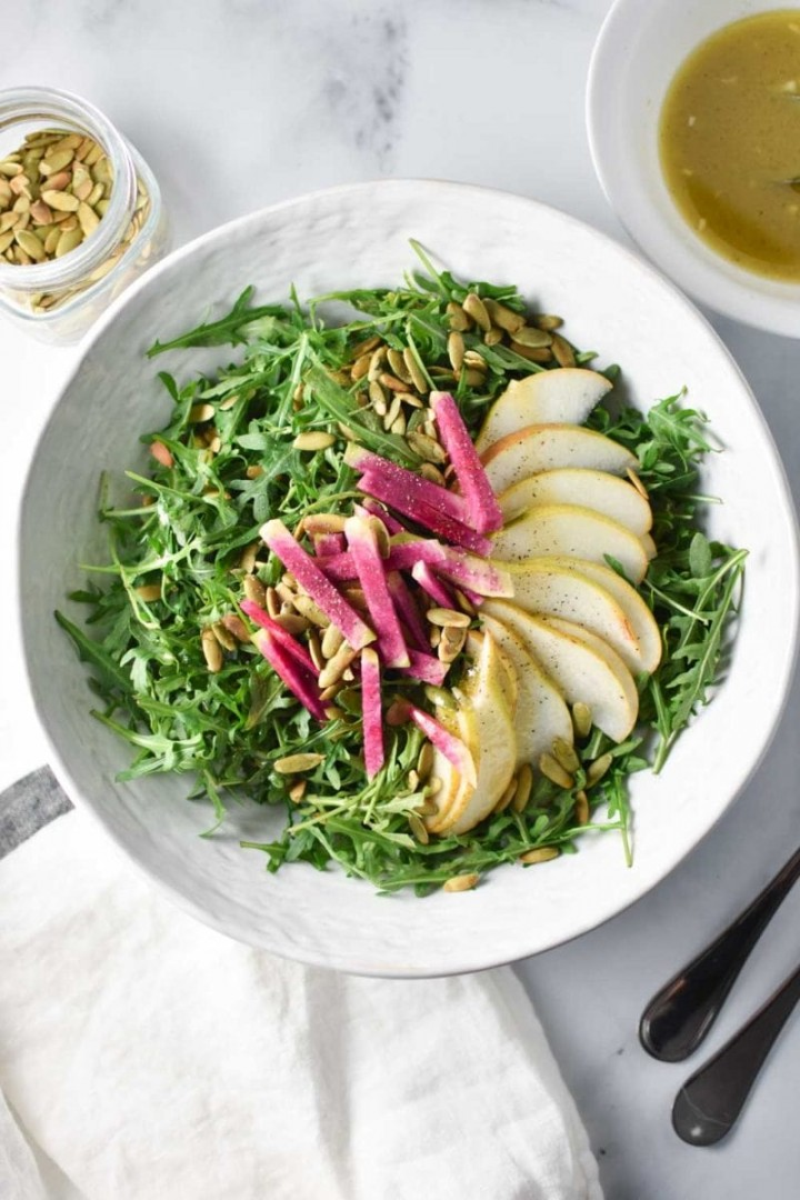 Arugula salad with pears and radish in a white bowl surrounded by pepitas and dressing