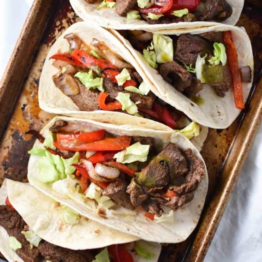 Quick and easy steak fajita recipe, perfect for a Friday night dinner. These flank steak fajitas are marinated in fresh (migraine safe) spices and cherry juice, which gives it the tart flavor without citrus. #fajitas #steak #migrainediet #recipe