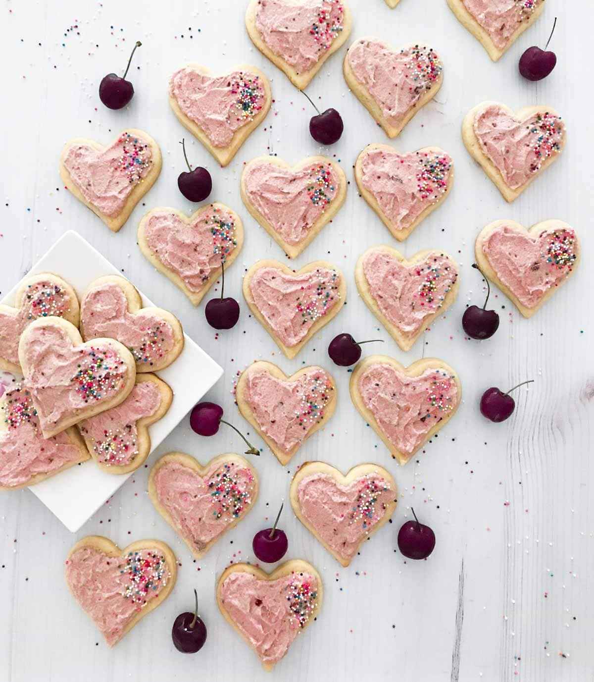 A plate of cherry sugar cookies and buttercream frosting with sprinkles scattered on top.