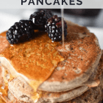 Maple syrup being poured on top of a stack of pancakes with fruit