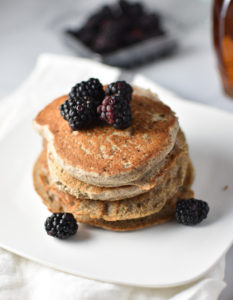 A stack of pancakes with blackberries on top and maple syrup in the background