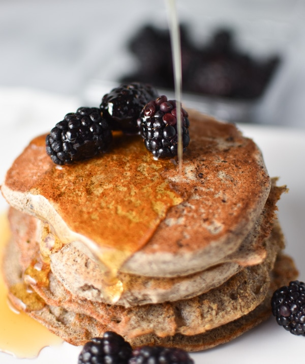 Maple syrup being poured onto a stack of buckwheat pancakes with blackberries