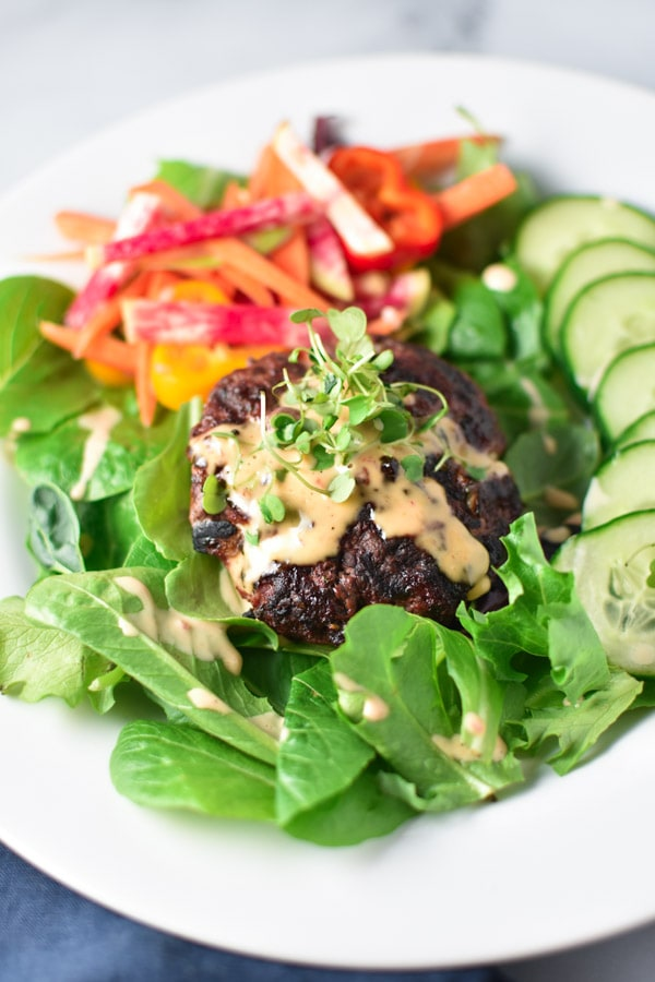 A burger salad topped with spicy mayo and microgreens