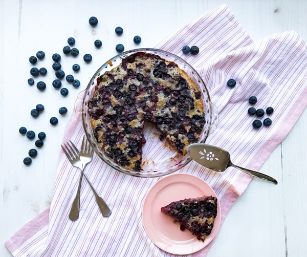 A crustless blueberry pie with a slice cut out and utensils on a pink striped towel