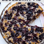 A crustless blueberry pie in a pie plate with a slice missing