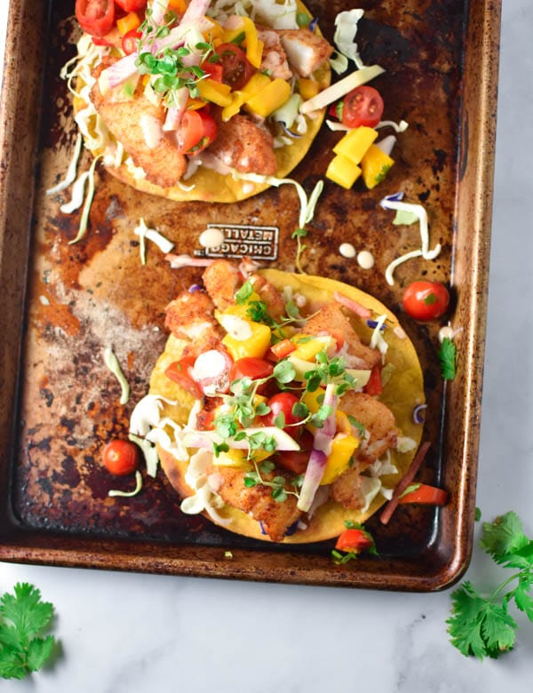 Fish tostadas topped with slaw and mangoes on a sheet pan with cilantro