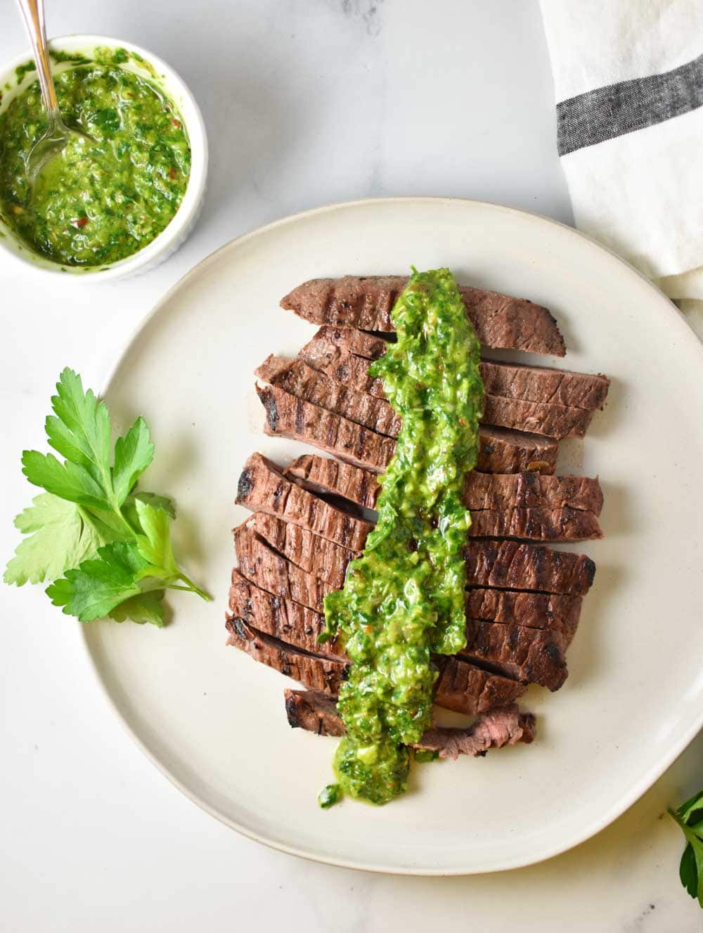 Sliced flank steak on a plate with chimichurri sauce on top and parsley