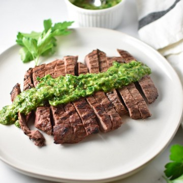 Grilled flank steak with a bowl of chimichurri in the back next to a towel