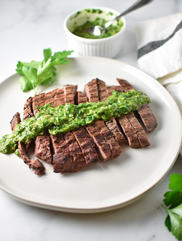 Sliced grilled steak with herb chimichurri on top on a marble table with a bowel of chimichurri in the background