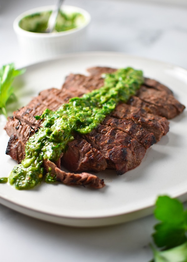 Flank steak sliced on a grey plate with green chimichurri sauce drizzled on top