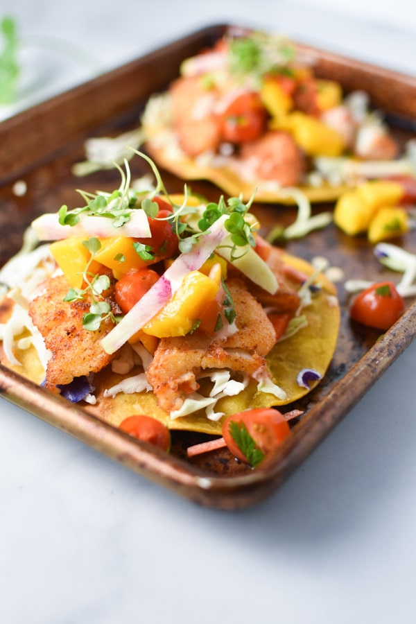 Close up of fried fish tostadas topped with microgreens on a white surface