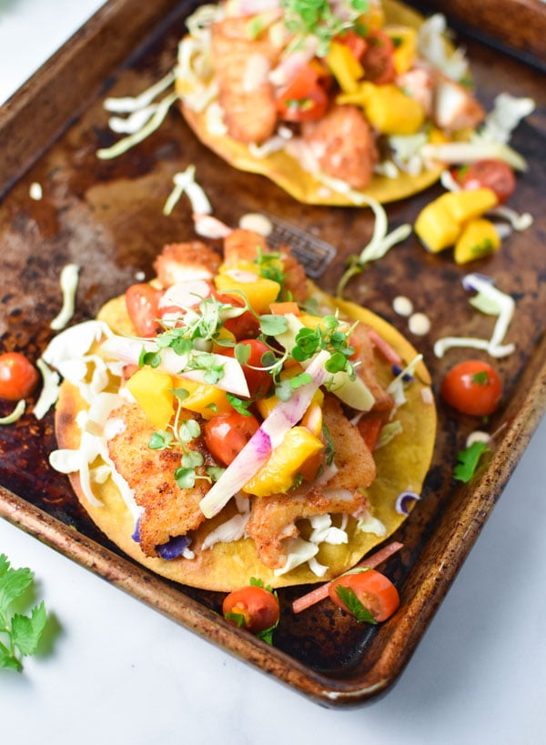 These crispy baja fish tostadas are topped with mango salsa and spicy mayo. These can be made gluten free with any kind of fish you like. #bajafish #tostadas #texmex #migrainediet