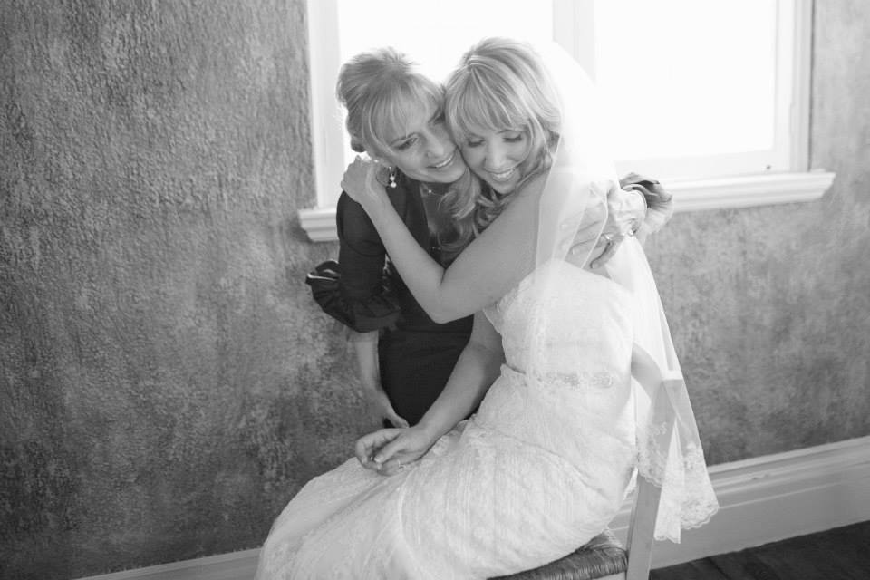 A mother and daughter hugging on a wedding day