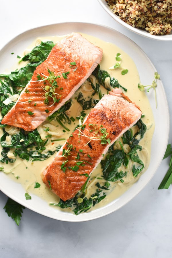 Seared salmon with creamed spinach on a marble table