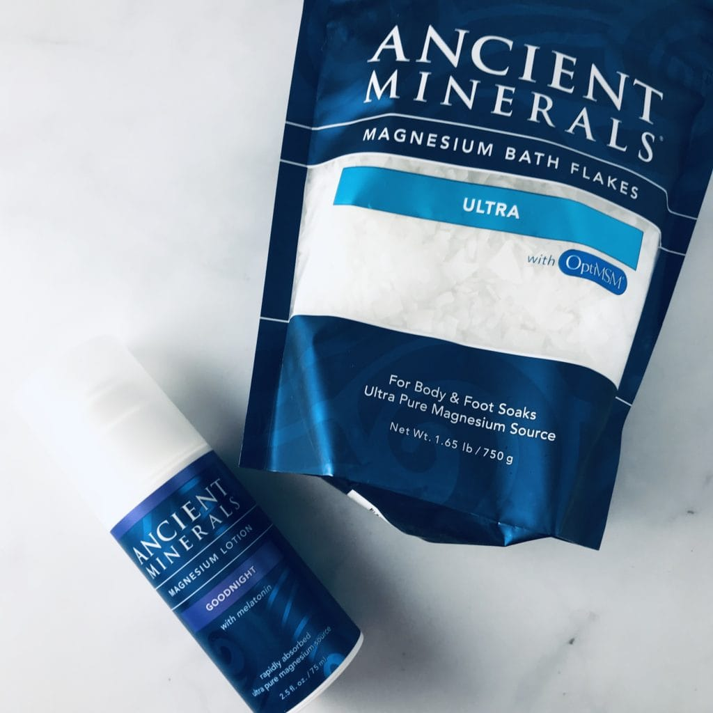 Ancient minerals magnesium bath flakes and lotion on a white surface
