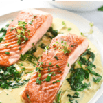This pan-seared salmon with creamy garlic spinach cooks in one pan and is decadent, yet easy to make. #glutenfree #salmon #easydinner #easyrecipes