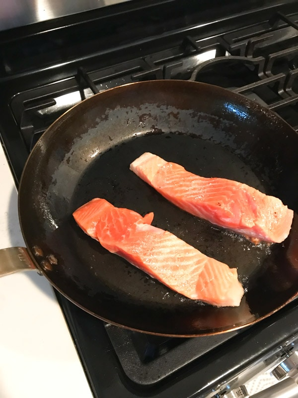 Two filets of salmon in a madein frying pan on a gas stovetop