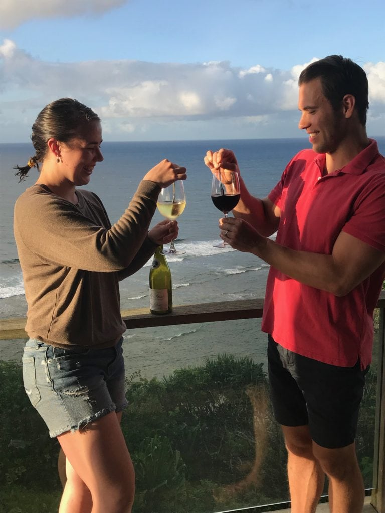 Two people stirring their wine with wine wands overlooking the beach