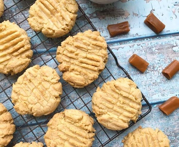 Caramel cookies on a cooling rack with a wood background and candies in a bowl