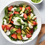 Burrata, peach, and strawberries in a salad bowl with basil vinaigrette in a white cup and tongs