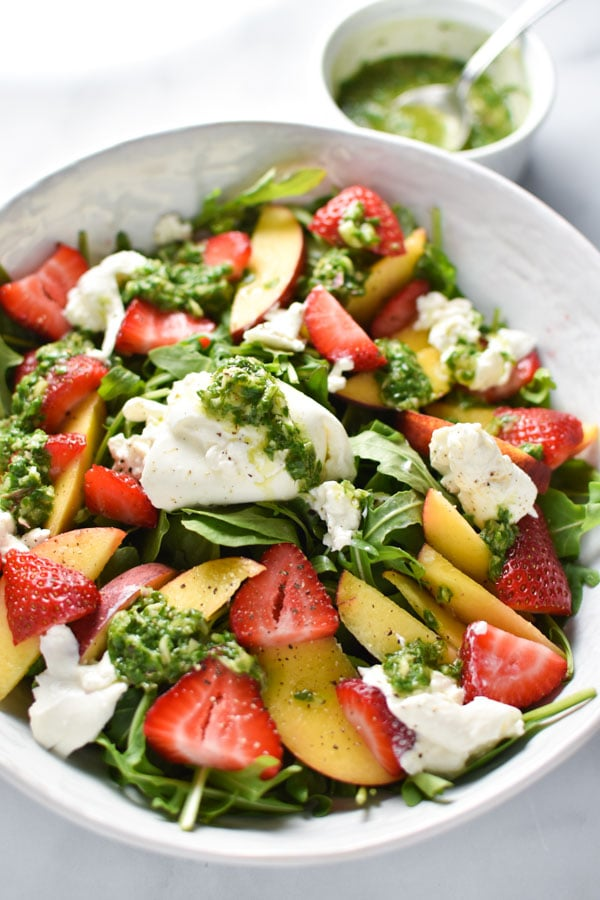 Peaches, strawberries, and burrata on arugula in a white bowl with a basil vinaigrette in the background