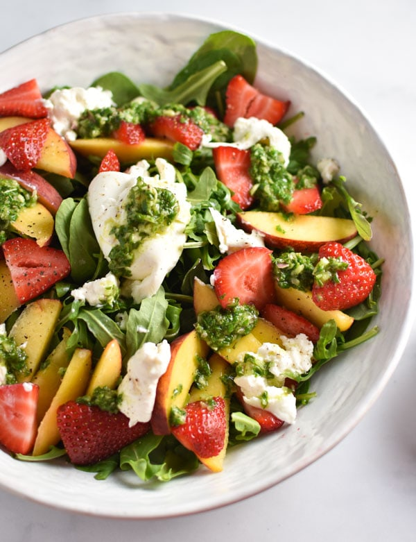 Burrata on top of a strawberry peach salad