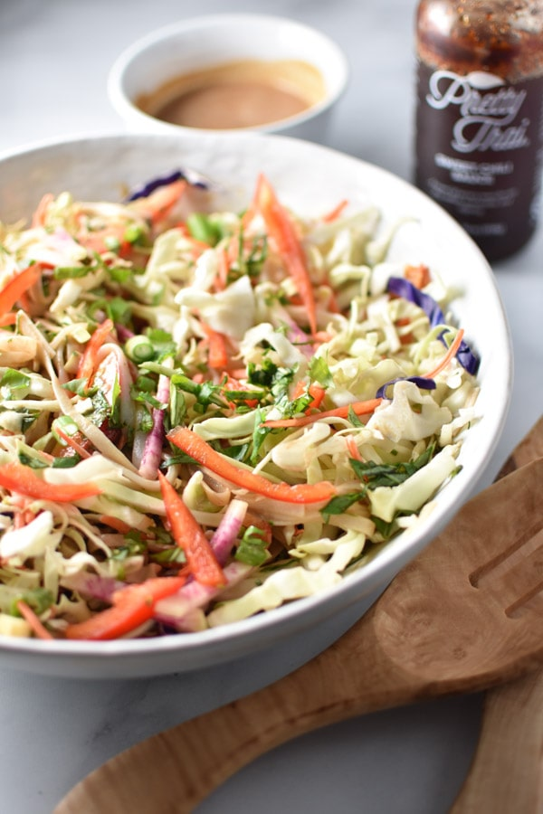 A large bowl of Thai noodle salad with carrots and peppers next to sweet chili sauce