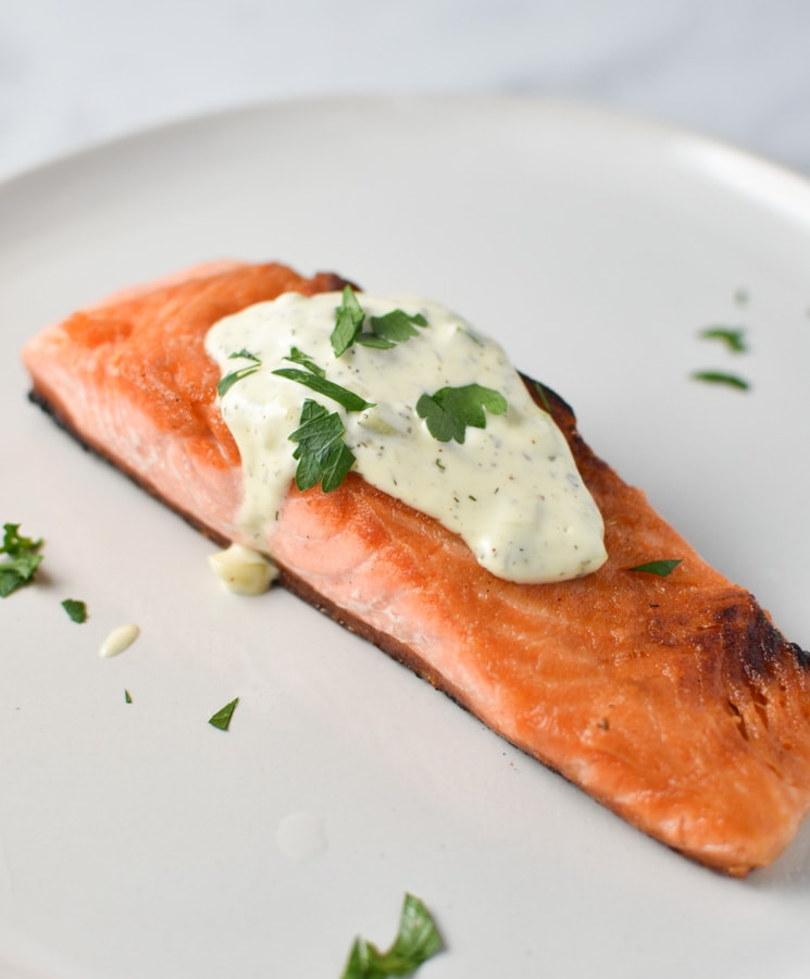 Seared salmon topped with tartar sauce on a grey plate