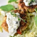 Close up of crab cakes with tartar sauce dripping down on a bed of lettuce