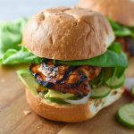 Up close of honey chipotle chicken sandwich with cucumber, lettuce, and shallots on a wood board