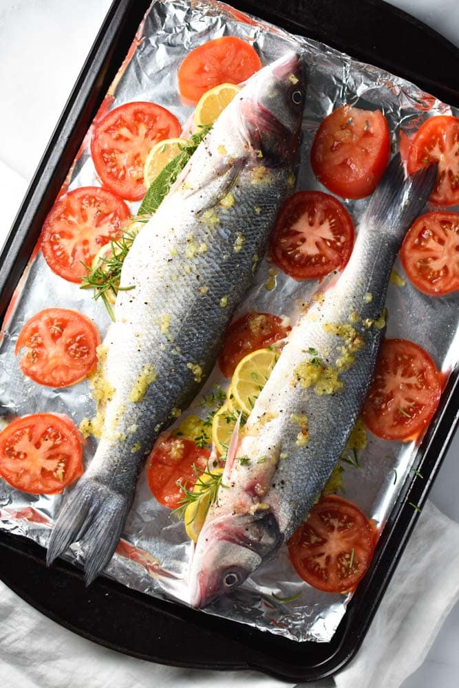 Fresh branzino stuffed with herbs and lemons surrounded by tomatoes
