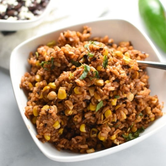Corn, rice, and black beans in a bowl with jalapenos