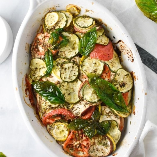 Roasted summer squash, zucchini, tomatoes, shallots, and herbs in a gratin dish with crispy basil