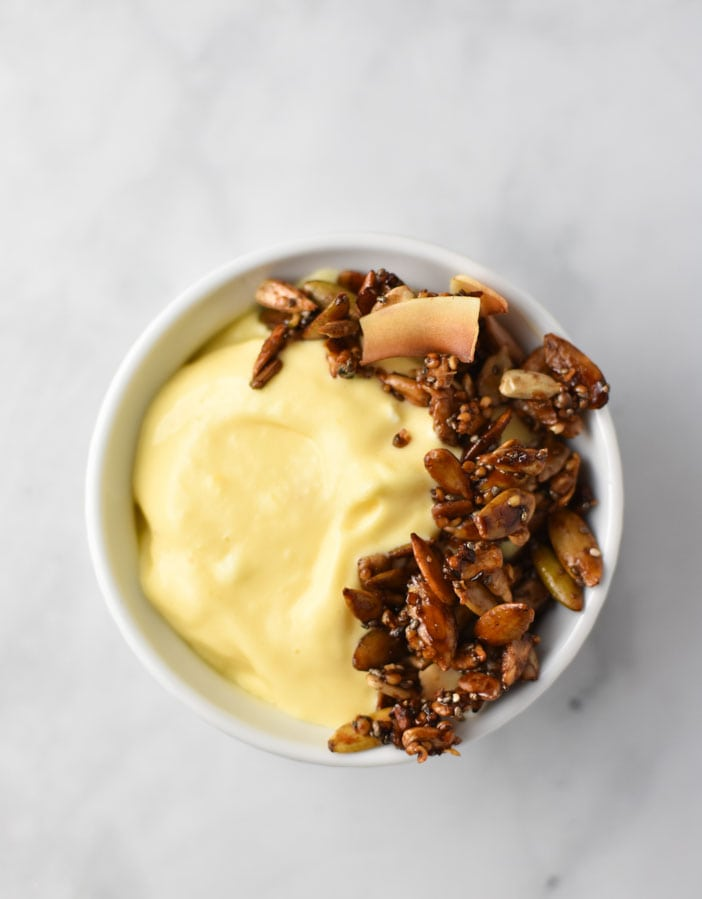 a white bowl with mango lassi smoothie and granola on top