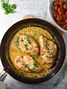 chicken breasts in a pan with cream sauce and tomatoes in a small white dish