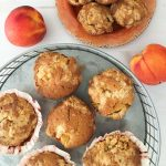 Light brown muffins on a orange plate surrounded by peaches and ginger