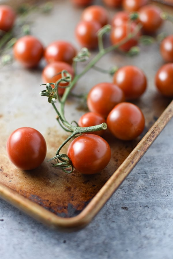 cherry tomatoes on the vine on a sheet pan