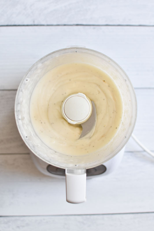 Whipped mayo in a food processor on a white board