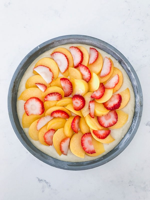 Peaches and strawberries layered on top of a cake in a silver cake pan on a white surface
