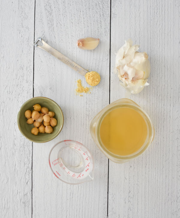 A bowl of chickpeas, garlic, mustard powder in a teaspoon, and a measuring cup with aquafaba on a wood background
